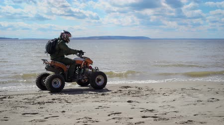 atv : Man dressed in protective equipment and helmet riding ATV and driving along the seashore with high speed. Fan of extreme tourism with backpack behind rushing on his quad bike on the beach.