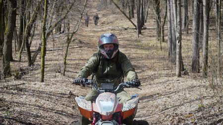 quadbike : Close up of a man in protective equipment and helmet operating ATV and moving along the road from side to side. Fan of extreme tourism riding quad bike on the path with people in the background.