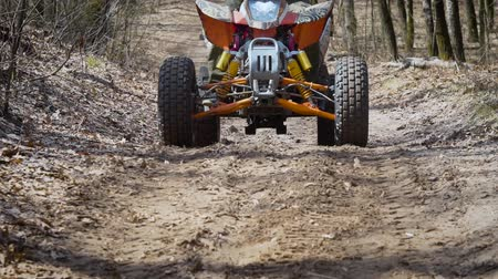 quadbike : Close up of a extreme rider in green protective equipment and helmet is operating ATV and moving along the road in the forest. Image of front side of quad off-road bike moving on the path. Stock Footage