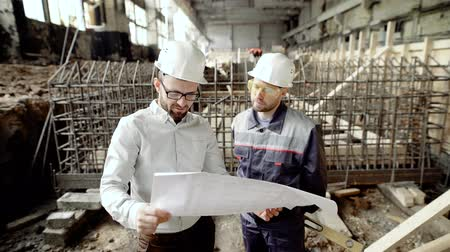 állványzat : A businessman and a professional worker look at the drawing in order to determine the possibility of upgrading the old factory building Stock mozgókép
