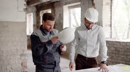 állványzat : A businessman in a helmet on his head and a professional construction discussing the blueprints of the building, the men are at the construction site Stock mozgókép