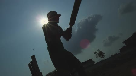 kriket : Silhouettes of young men ready to playing cricket in a park in Chennai, India