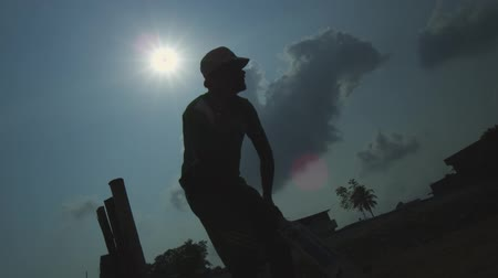 batedor : Silhouettes of young men playing cricket in a park in Chennai, India Stock Footage