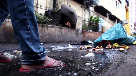 kanalizacja : Young boy walking on sewerage slam street, Closeup leg shot.