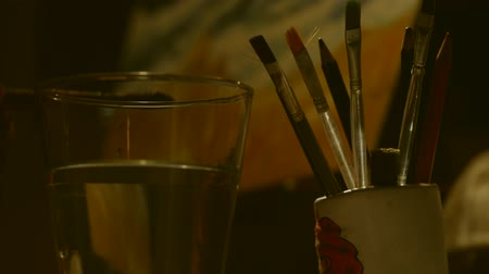 boyalar : Man painting and Dipping Paint Brush In Water Glass. Stok Video