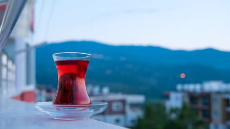 ramadan : Reflection and light of sky with turkish cup of tea during sunset from day to night time lapse in Turkey, Tilt down timelapse motion.