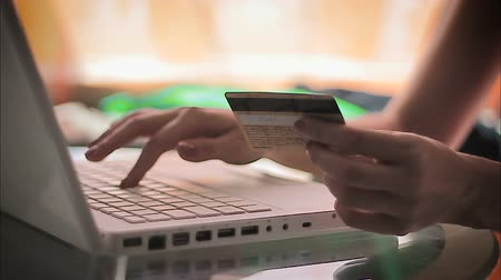organizer : Woman entering information from a credit card using laptop, closeup shot