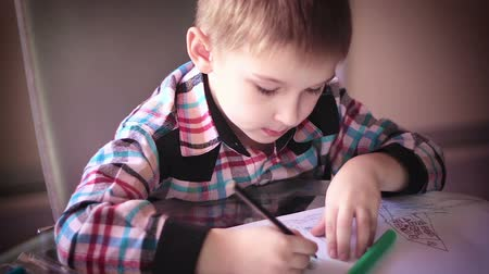 vista frontal : Little boy sitting at table and drawing with colored pencils Stock Footage