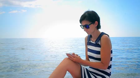 telefone celular : Young woman using cellphone on sea background Stock Footage