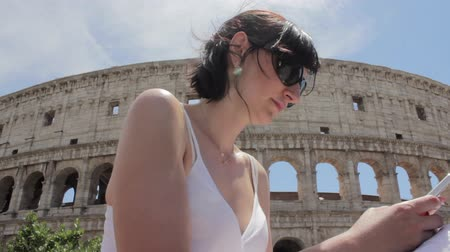colosseum : Young caucasian woman tourist texting on beautiful view of european ancient city with mobile smart phone