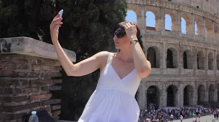 colosseum : Young caucasian woman tourist make selfie on beautiful view of european ancient city with mobile smart phone Stock Footage