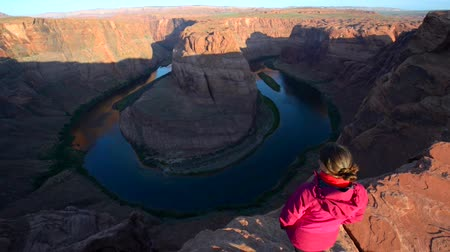 тур : Girl hiker standing at the edge of Horseshoe Bend Page arizona looking down at Colorado River Стоковые видеозаписи