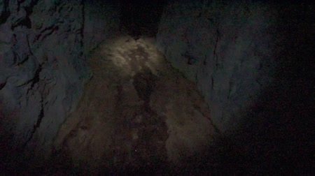 Walking inside dark gold mine shaft