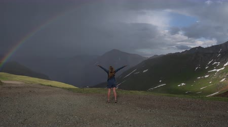 Happy traveler girl raises her hands up shows the rainbow Colorado Mountains Стоковые видеозаписи