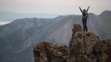 Woman Backpacker raises her arms up after climbing on top of the mountain