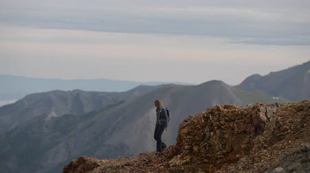 Girl Hiker walks along steep mountain ridge San Juan Mountains Colorado