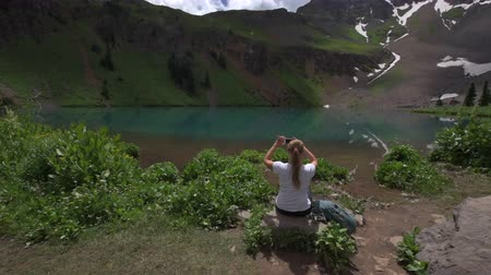 Backpacker Girl takes pictures with her smartphone at Lower Blue Lake  Ridgway Colorado Стоковые видеозаписи