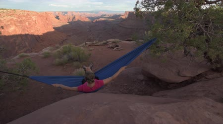 moab : Hiker rests on a hammock admiring the sunset East Fork Shafer Canyon near Dead Horse Point State Park Canyonlands Utah USA