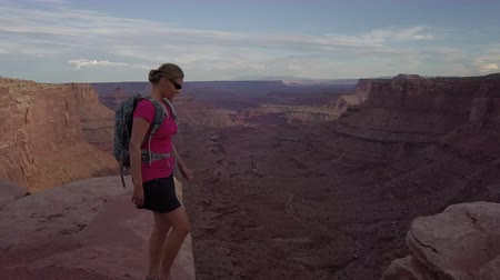 aro : Backpacker Girl walks along the Rim of East Fork Shafer Canyon near Dead Horse Point State Park Canyonlands Utah USA Stock Footage
