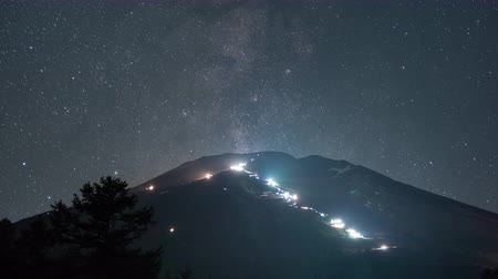 домик : Milky Way over Mt. Fuji: Lights moving on the mountain are of climbers  flashlights and brighter lights are of the lodges Стоковые видеозаписи