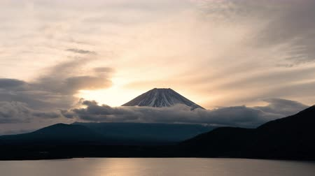 trave : Mt. Fuji over Lake Motosu at Sunrise: the view of Mt. Fuji over lake Motosu is famous for being printed on the back of the 1000 yen note (time lapsezoom in) Stock Footage