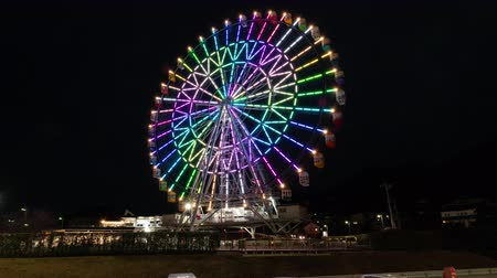 built : Illuminated Ferris Wheel Turning around against the Night Sky (lapsezoom in time)