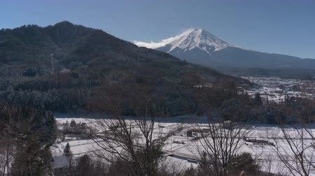 snowcapped : Mt. Fuji over a Snowy Village and Mountain (time laps)