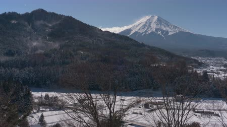 rüzgârla oluşan kar yığını : Mt. Fuji over a Snowy Village and Mountain (pan) Stok Video