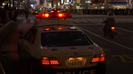 yaşama gücü : EDITORIAL: Shibuya Ward, TokyoJapan-February 12, 2019: A police car parked near the Shibuya Crossing. Theres a police box right next to the car in the left (time lapse)