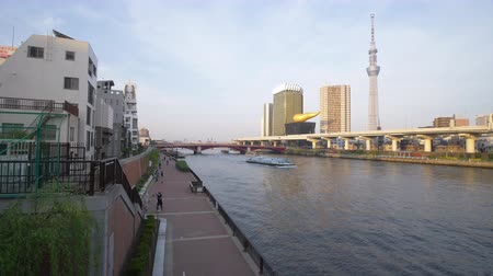 bank tower : Asakura, Taito-ward, Tokyo, Japan-April 22, 2018: Tokyo Skytree over the Sumida River, people walkingjogging in the Riv Erside Park, and pleasure boats going updown the river.