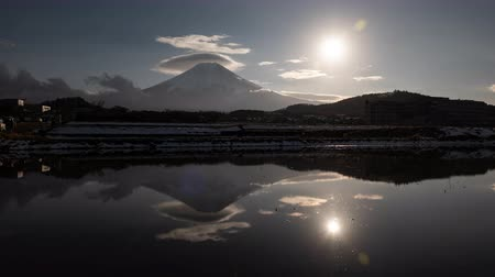 явление : Mt. Fuji with Lenticular Clouds and the Sun Reflected in a Water-Filled, Empty Rice Field (Time Lapse) Стоковые видеозаписи
