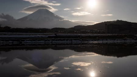 явление : Mt. Fuji with Lenticular Clouds and the Sun Reflected in a Water-Filled, Empty Rice Field (time lapsepanning) Стоковые видеозаписи