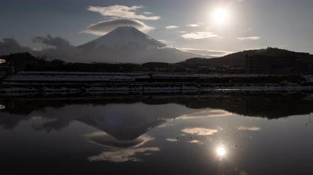 явление : Mt. Fuji with Lenticular Clouds and the Sun Reflected in a Water-Filled, Empty Rice Field (time lapsezoom in)