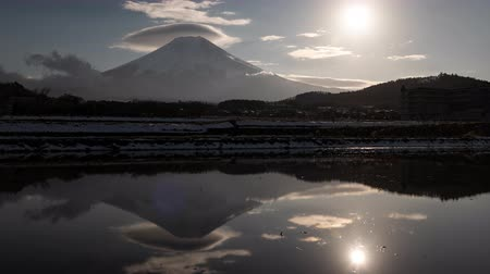 явление : Mt. Fuji with Lenticular Clouds and the Sun Reflected in a Water-Filled, Empty Rice Field (time lapsezoom out)