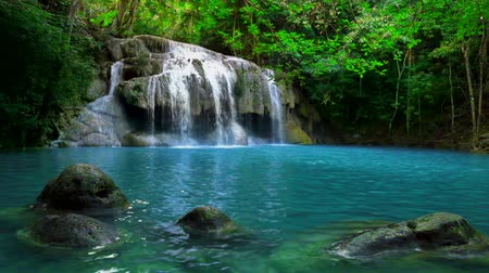 esőerdő : Jangle landscape with flowing turquoise water of Erawan cascade waterfall at deep tropical rain forest. National Park Kanchanaburi Thailand Stock mozgókép