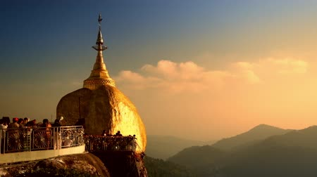 туристическим направлением : Burmese people praying near Golden Rock at sunset. Most sacred Buddhist place with rock balancing on three hairs of Buddha. Myanmar Burma travel