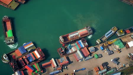 industry : HONG KONG - JAN 23, 2015: Cargo ships loaded by crane with cargo containers at a busy port terminal. Hong Kong video form aerial view point Stock Footage