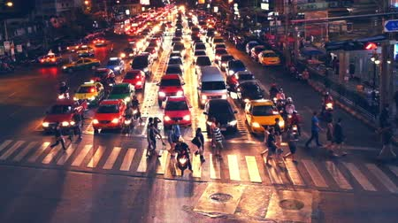 zsúfolt : BANGKOK, THAILAND - DEC 13, 2014: People moving at crossroad in crowded evening city street. Bangkok, Thailand Stock mozgókép