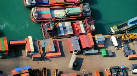truck crane : Cargo ships loaded by crane with cargo containers at a busy port terminal. Hong Kong video form aerial view point
