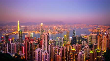 panorâmico : Tilt shift blur effect. Aerial panorama view of Hong Kong skyline at sunset. Modern financial and cultural asian city at Victoria Harbor. Time lapse
