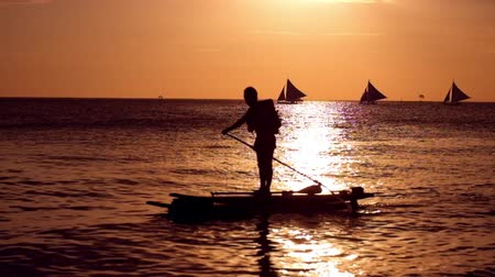 remo : People on vacation, enjoying the amazing sunset at tropics. Sail boats silhouettes floating on ocean horizon Boracay island. Philippines travel Vídeos