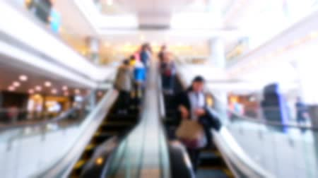 запачканный : People on moving escalators at modern shopping mall, Hong Kong. Blurred fast speed video, unrecognizable people