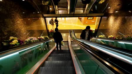életmód : HONG KONG - JAN 15, 2015: People on moving escalators at modern shopping mall