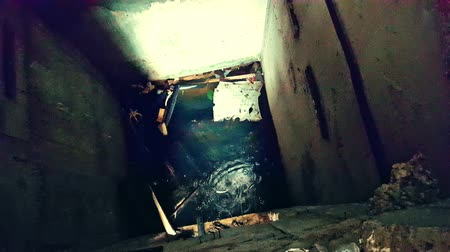 abandoned house : Camera comes close to flooded elevator shaft and looks down at water, dripping drops and debris. Post-apocalyptic ruins. Found footage horror movie scene. First-person perspective, live cam view.