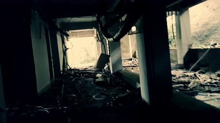 decadência : Shaky camera moves between gray concrete columns in destroyed abandoned building full of debris and wiring hanging from ceiling. Depressing movie scene. Post-apocalyptic concept. Live cam view.