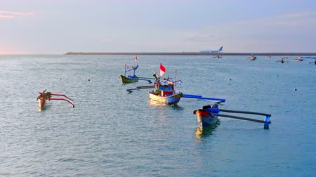 fishermen : Moored outrigger fishing vessels with Indonesian flags waving in wind against beautiful sunset sky with setting sun and Ngurah Rai airport runway with landed airplanes on background. Camera zooms out. Stock Footage