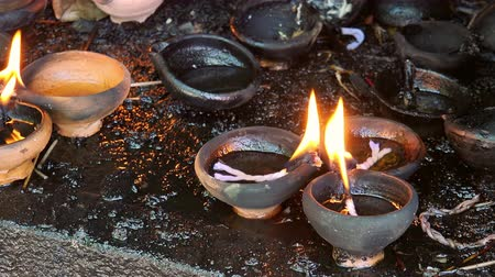 incenso : Zooming video of burning oil lamps and incense joss sticks at temple. Traditional offering in buddhist and hindu temples
