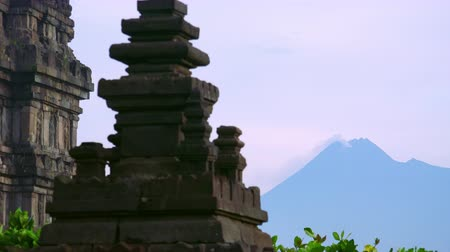 emit : Stone tower of Prambanan Hindu temple with Merapi volcano on background. World heritage site, ancient place of worship, popular tourist attraction. Yogyakarta, Central Java, Indonesia. Panning shot.