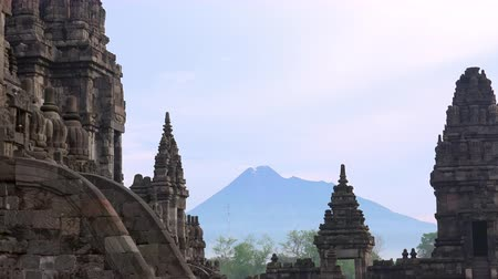 emit : Gorgeous shrines of Candi Prambanan temple complex against active volcano Mount Merapi emitting smoke into air and morning sky on background. Yogyakarta, Central Java, Indonesia. Camera zooms out.