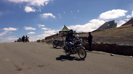 TAGLANG LA, INDIA - SEPTEMBER 13, 2017: Motorcyclist rides bike past camera, greets it and waves hand on Tanglang La high mountain pass. Motorcycle riders on Leh–Manali Highway on sunny day. Стоковые видеозаписи